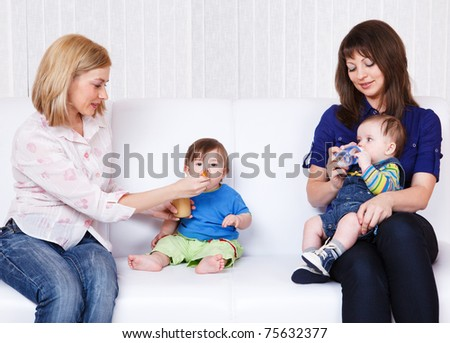 Cheerful mothers feeding babies in the living room - stock photo