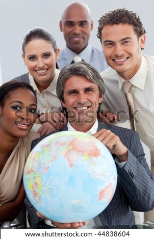 Cheerful Multi-ethnic business team showing a terrestrial globe in the office - stock photo