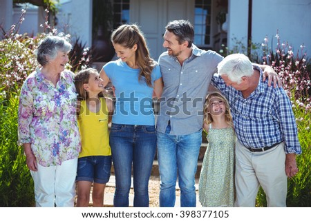 Cheerful multi-generation family looking at each other against house - stock photo