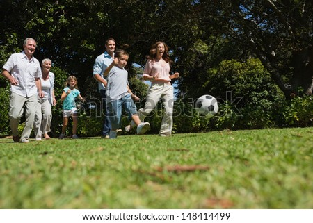 Cheerful multi generation family playing football in the park - stock photo