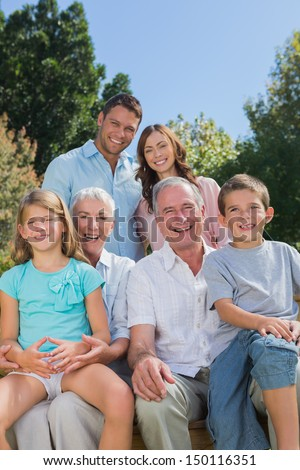 Cheerful multi generation family sitting on a bench in park looking at camera
