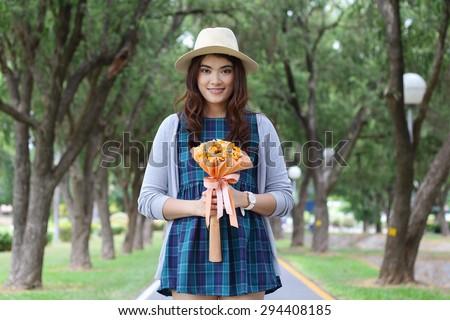 Cheerful multiracial Asian woman wearing a hat - stock photo