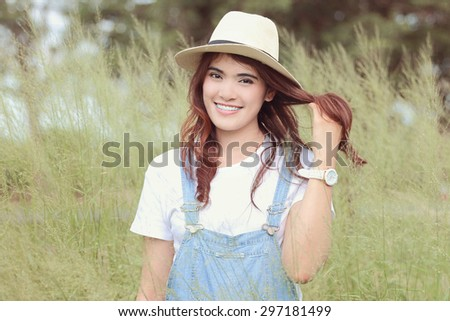 Cheerful multiracial Asian woman wearing a hat in the grassland, red soft tone - stock photo