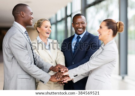 cheerful multiracial business team putting their hands together - stock photo