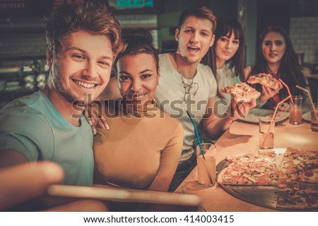 Cheerful multiracial friends having fun eating in pizzeria.