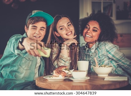 Cheerful multiracial friends taking selfie in a cafe  - stock photo