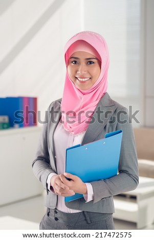 Cheerful Muslim business woman with a folder looking at the camera - stock photo