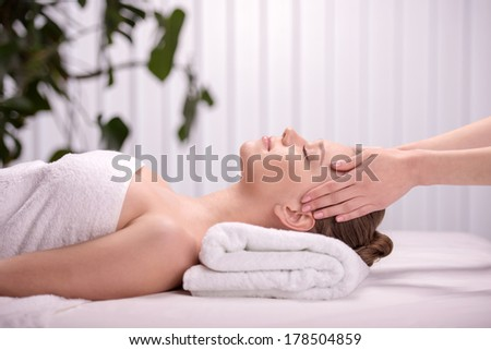 Cheerful naked young woman lying on front receiving message