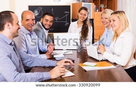 Cheerful office staff gathered in the conference hall for the meeting - stock photo