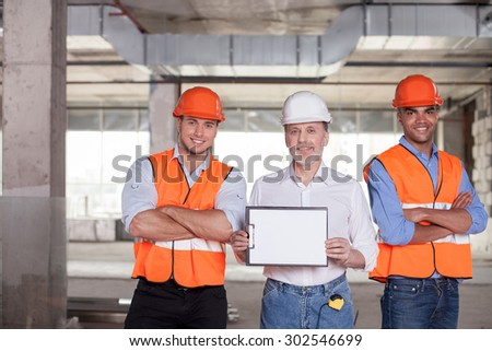 Cheerful old architect is showing a folder of white empty paper to the camera. Two handsome builders are standing near him. They crossed hands. The men are smiling - stock photo