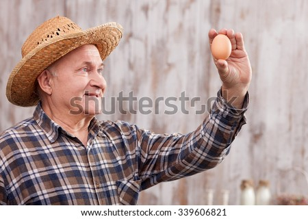 Cheerful old farmer is holding an egg and looking at it with concentration. The man is standing and smiling. He is wearing a straw hat - stock photo