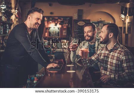 Cheerful old friends drinking draft beer at bar counter in pub. - stock photo