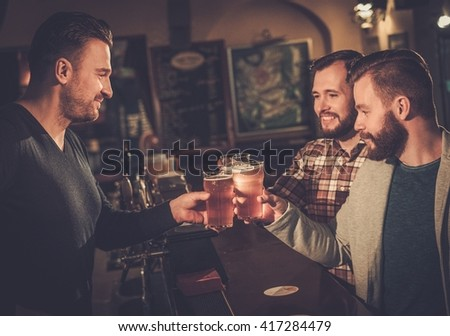 Cheerful old friends drinking draft beer at bar counter in pub.