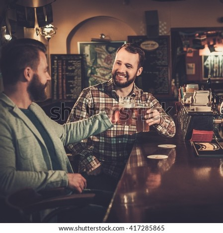 Cheerful old friends having fun and drinking draft beer at bar counter in pub. - stock photo