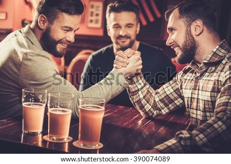 Cheerful old friends having fun arm wrestling each other in pub. - stock photo