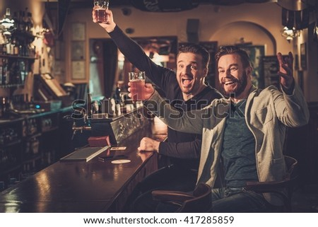 Cheerful old friends having fun watching a football game on TV and drinking draft beer at bar counter in pub. - stock photo