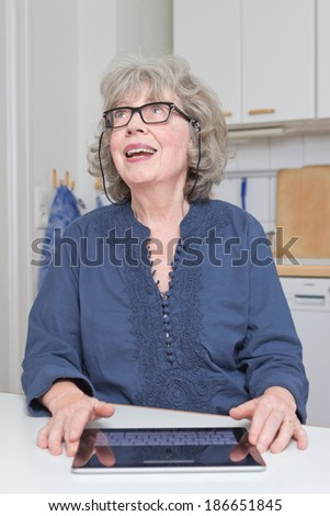 Cheerful old lady with touch pad in kitchen, having a good idea