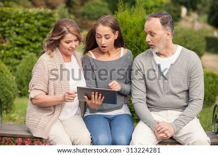 Cheerful old man and woman are spending time with their adult daughter. They are sitting on a bench in park. The girl is holding a tablet. They are looking at it with surprise - stock photo