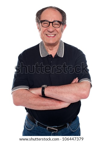 Cheerful old man standing with arms crossed against white background - stock photo