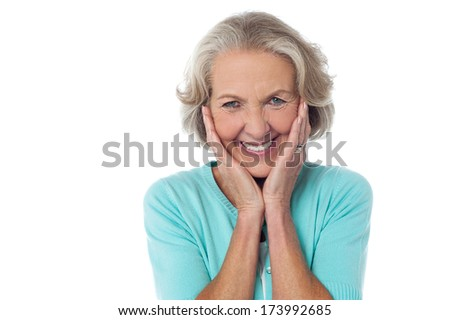 Cheerful old woman with hands on her cheeks
