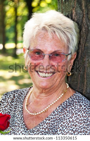 cheerful older senior citizen with a red rose. - stock photo