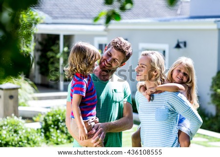 Cheerful parent carrying children in yard against house - stock photo
