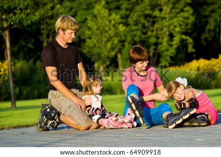 Cheerful parents and kids in roller skates - stock photo