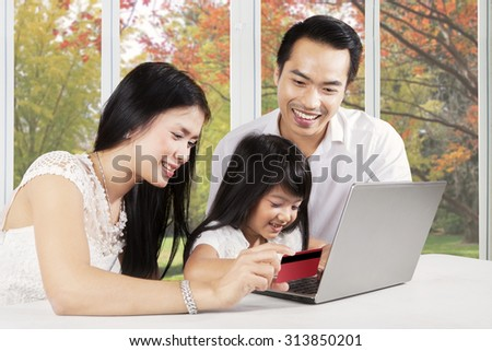 Cheerful parents and their daughter using laptop and credit card for shopping online at home with autumn background on the window - stock photo
