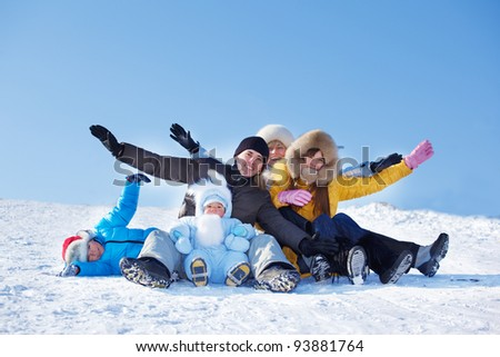 Cheerful parents and their kids sit on snowy hill - stock photo