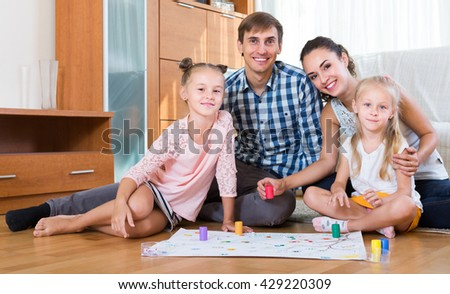 Cheerful parents and two daughters with board game at home - stock photo