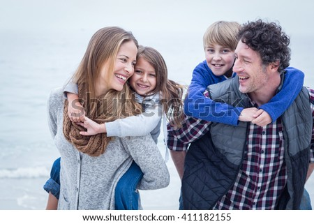 Cheerful parents carrying children on back at beach - stock photo
