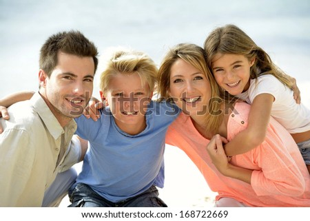 Cheerful parents holding kids on their back - stock photo