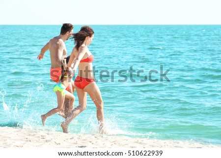 Cheerful parents playing with little girl in water