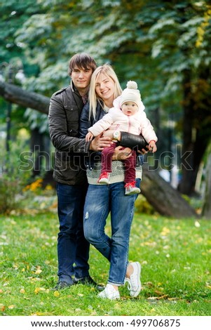 Cheerful parents with child standing in autumn park