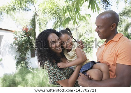 Cheerful parents with daughter enjoying together in park - stock photo
