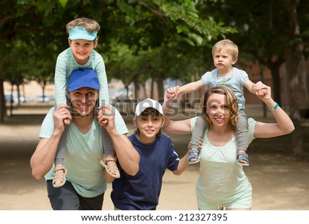 Cheerful parents with kids staying outdoor and smiling - stock photo