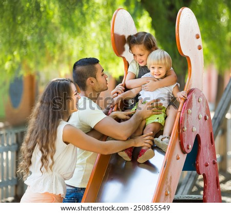 Cheerful parents with two daughters playing at children's slide  - stock photo
