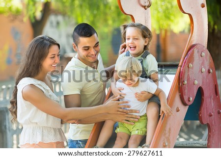 Cheerful parents with two daughters playing at children's slide. Focus on man  - stock photo