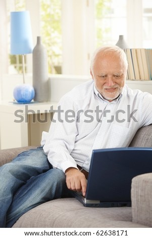 Cheerful pensioner using laptop computer on couch, looking at screen, smiling.? - stock photo