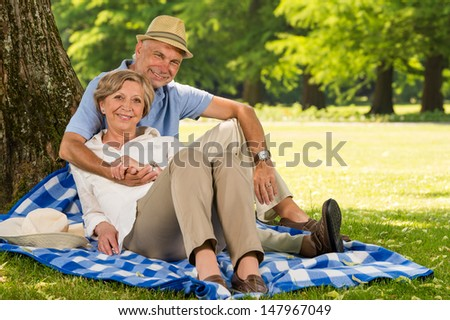 Cheerful pensioners hugging and relaxing outdoors sunny park - stock photo
