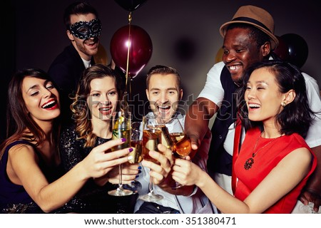 Cheerful people clinking with flutes of champagne - stock photo