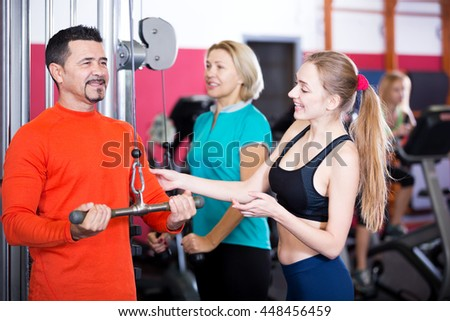 Cheerful people of different age having strength training in gym