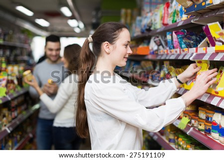 Cheerful people standing near shelves with canned goods at shop