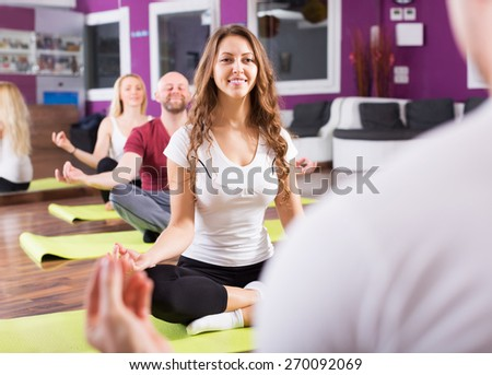 Cheerful people studying new position at yoga school - stock photo