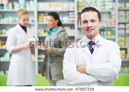 cheerful pharmacist chemist man standing in pharmacy drugstore - stock photo