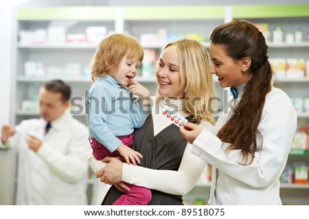 Cheerful pharmacist chemist woman giving vitamins to child girl in pharmacy drugstore - stock photo
