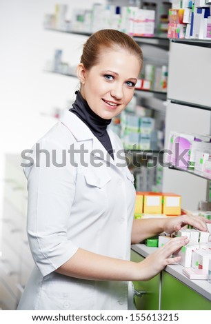 cheerful pharmacist chemist woman standing in pharmacy drugstore - stock photo