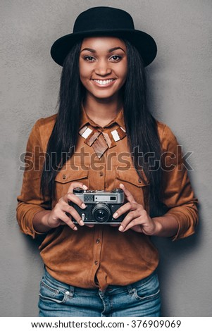 Cheerful photographer. Beautiful cheerful young African woman holding retro styled cameraand looking at camera with smile while standing against grey background - stock photo