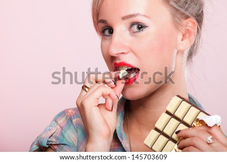 Cheerful pin up girl retro style portrait pinup Woman eating chocolate pink background - stock photo