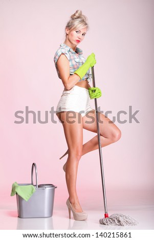 Cheerful pin up girl retro style portrait pinup Woman housewife cleaner mop pink background full lenght - stock photo